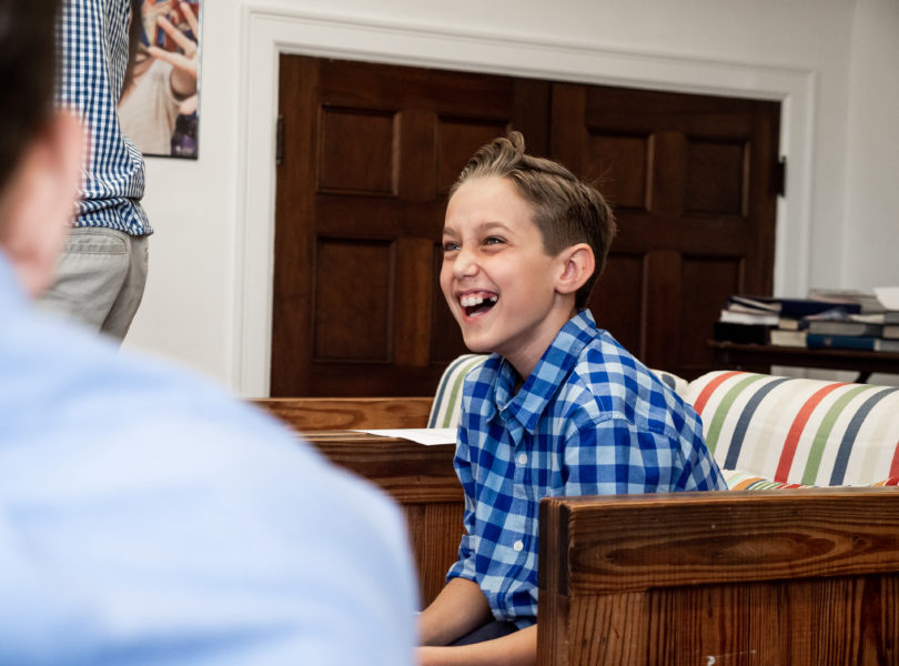 A boy laughs during middle school youth group