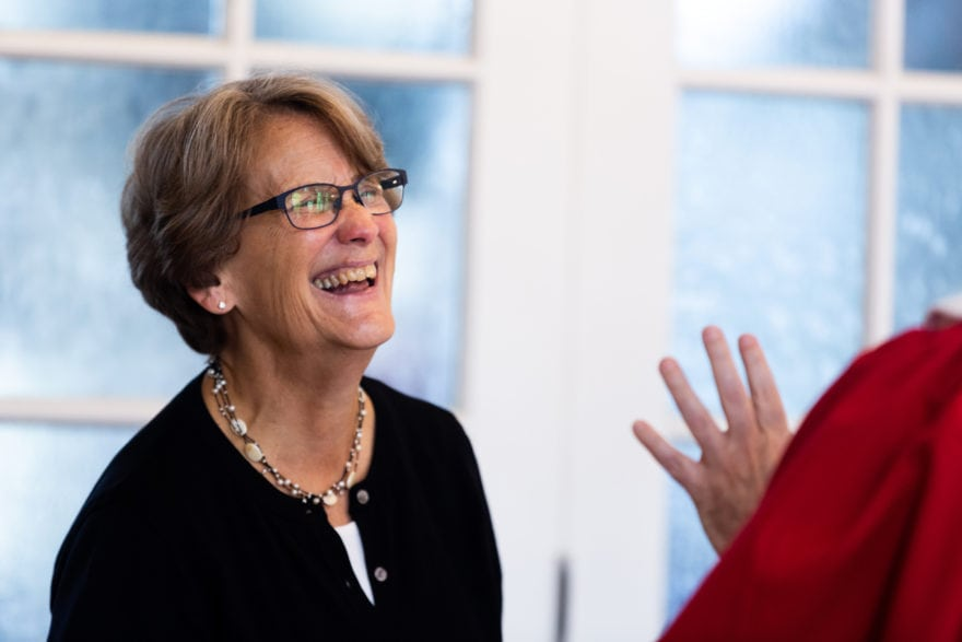A woman smiling while engaged in conversation