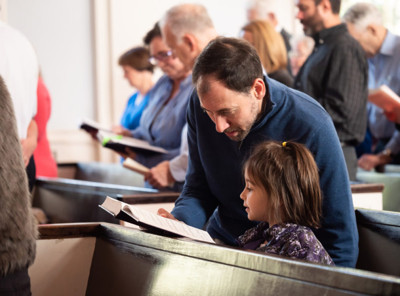 A father and daughter sing hymns together in church