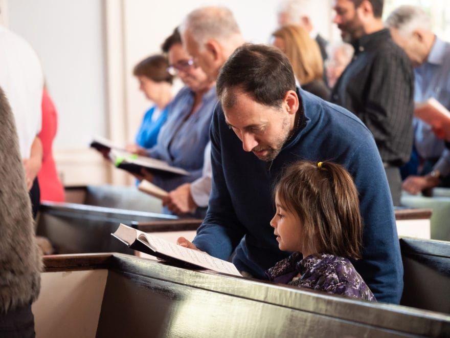 A father and daugher sing hymns together in church