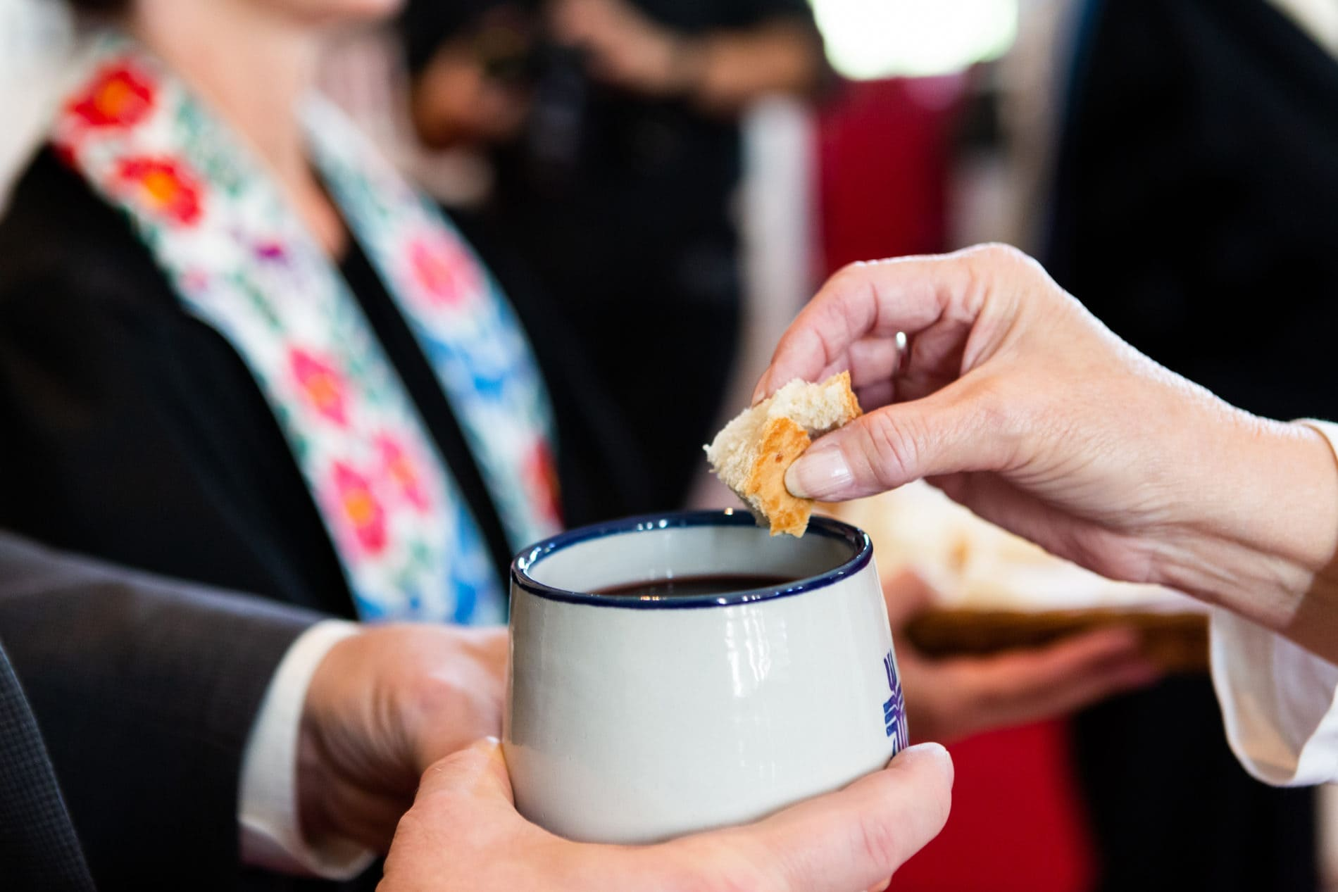 A person dips bread into a chalice during the eucharist