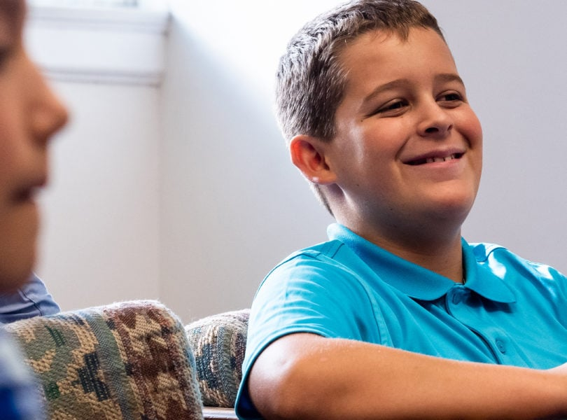 A middle school aged boy smiling during Sunday School