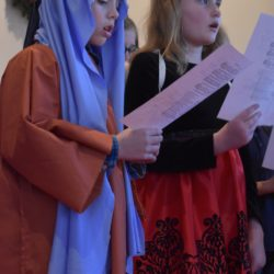 Two youth sing during the Christmas Eve worship service