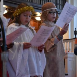 Two youth dressed as an angel and a shepherd sing during the Christmas Eve worship service