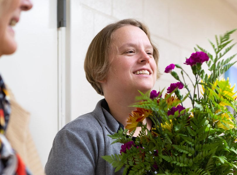 A woman delivers flowers to a nursing home.