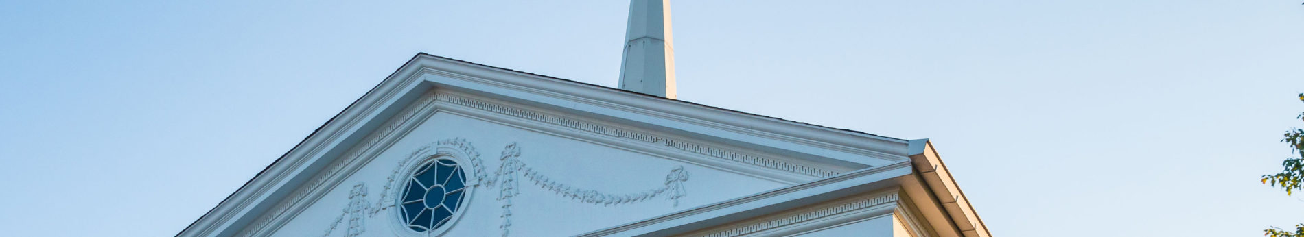 Exterior detail shot of Catonsville Presbyterian Church, showing roofline, decorative window, and steeple.