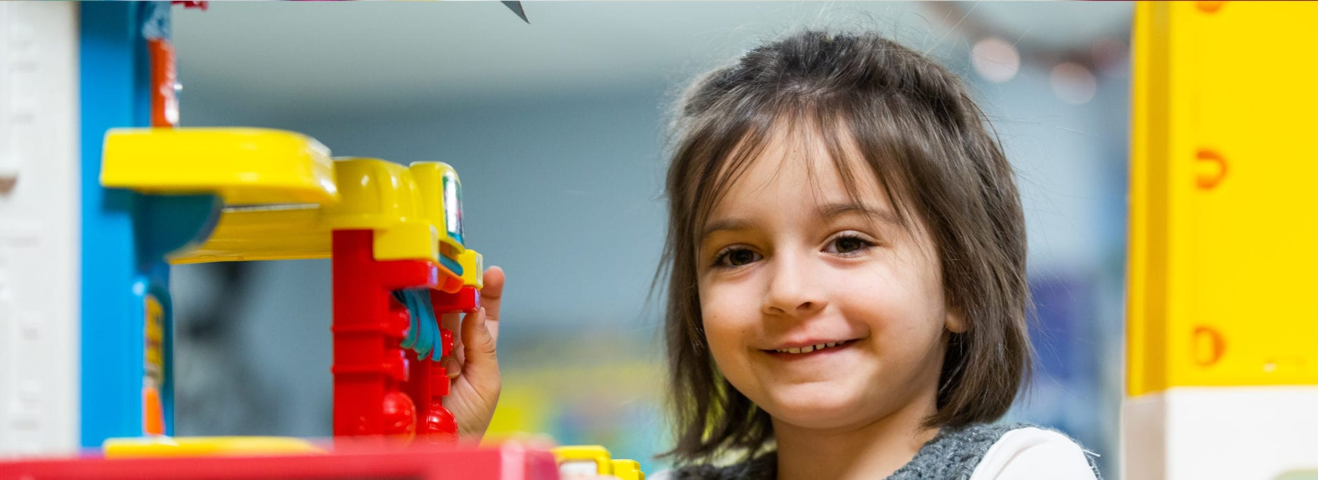A preschooler smiles while she plays with toys