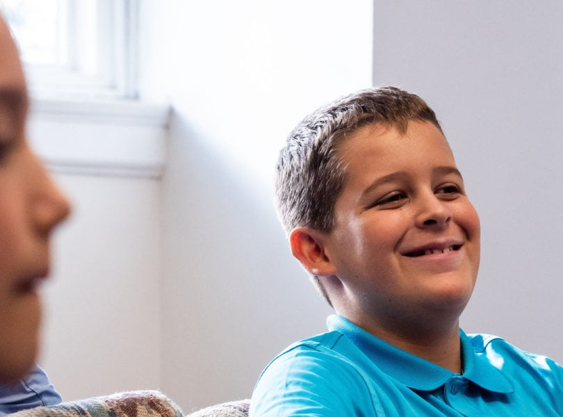 A pre-teen boy smiles during Sunday School.