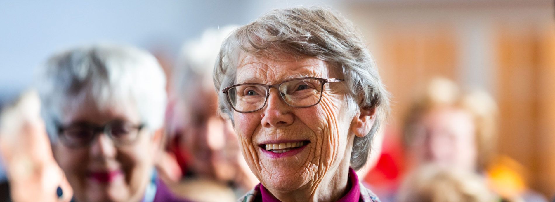 An elderly woman smiles in worship