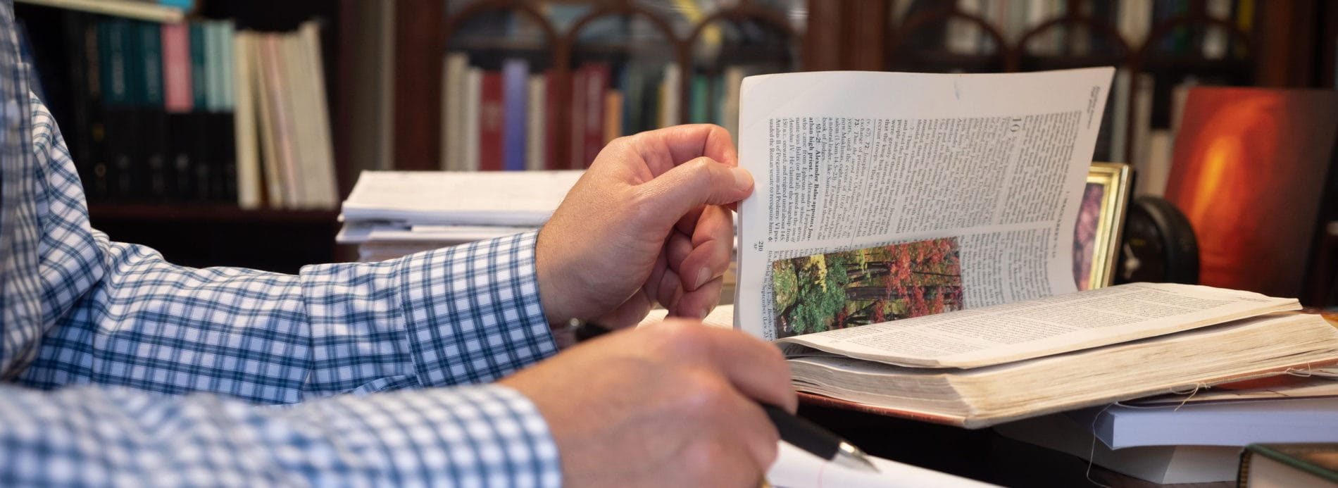 Rev. Ken Kovacs consults a scholarly text while preparing for a sermon