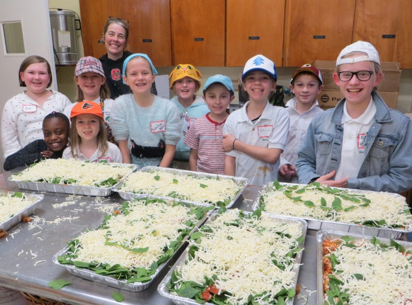 Elementary school youth smile with the casseroles they assembled for the shelter