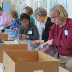 An assembly line packs Safe Motherhood Kits from boxes of supplies.