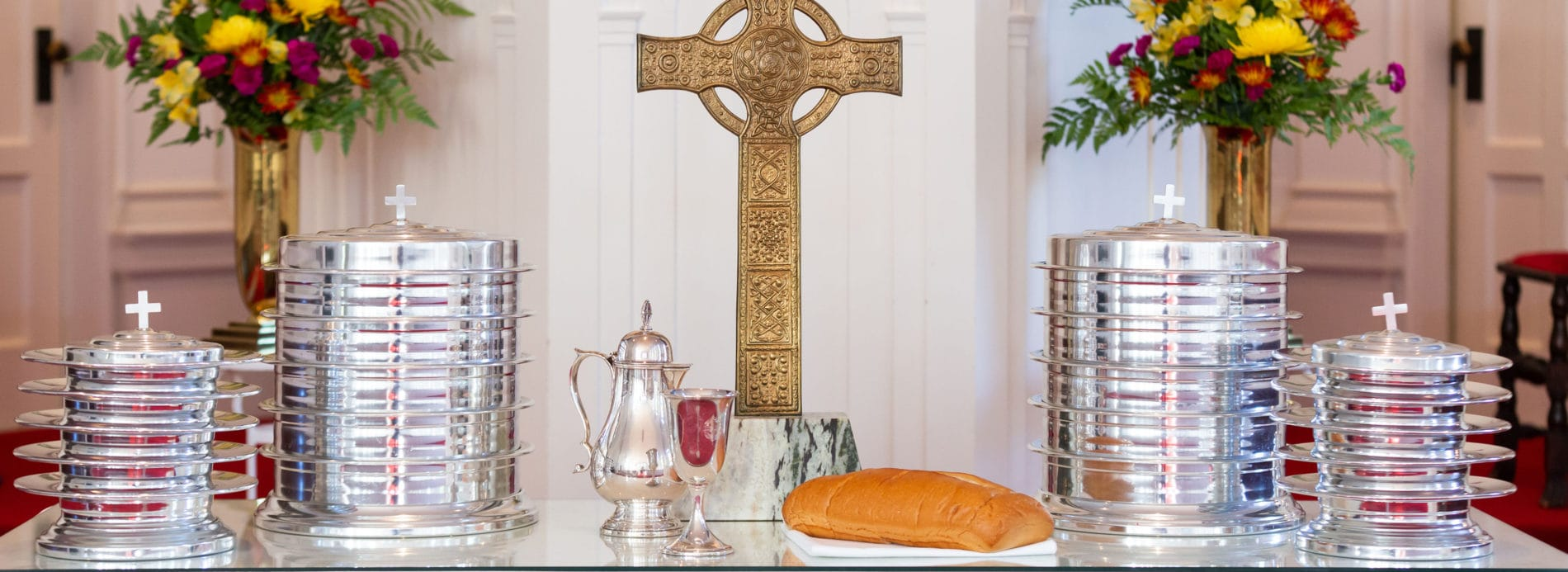 A communion table set with silver. A gold cross in the background.
