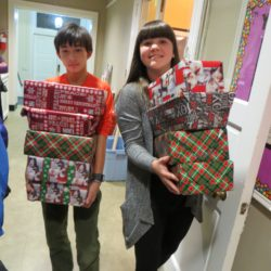 Two youth carry wrapped Christmas gifts for Baltimore Seafarers