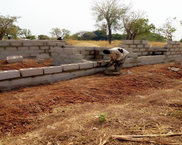 A construction worker builds a concrete block wall in Nigeria.