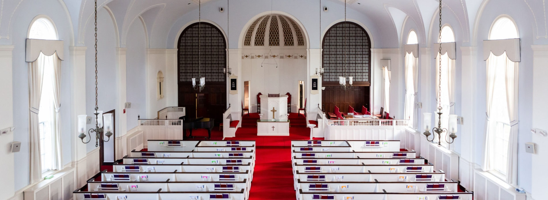 Interior view of the sanctuary of Catonsville Presbyterian Church, showing white pews, red carpet, and ornate chancel.
