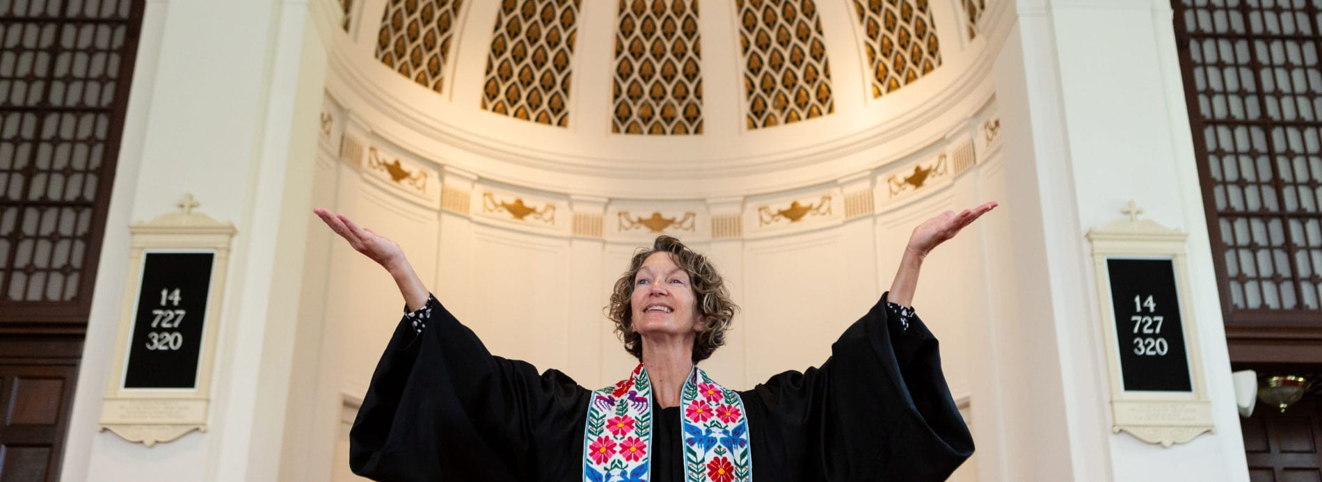 Rev. Dorothy Boulton lifts her arms and smiles as she leads worship.