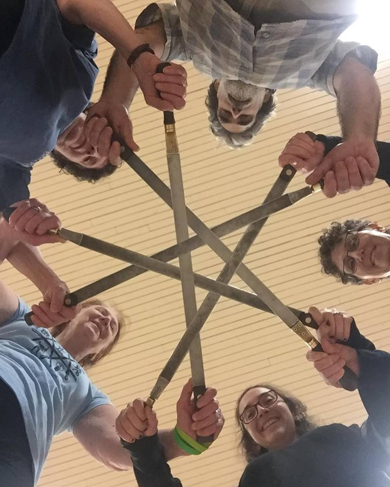 5 people stand in a circle holding swords to form the shape of a star
