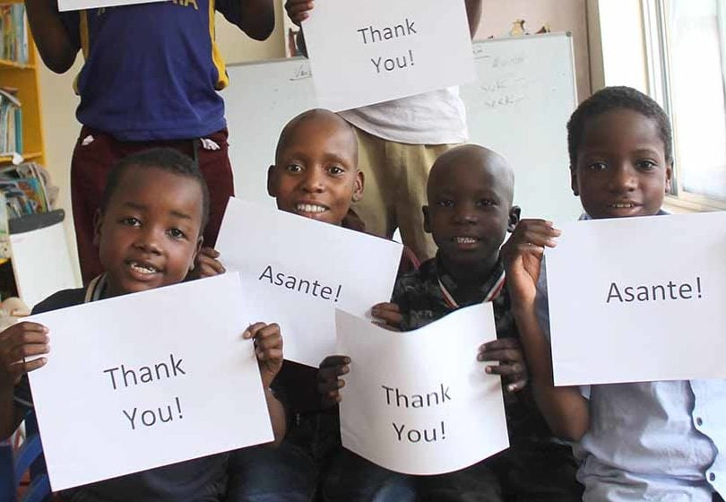 Tanzanian children hold signs that say,