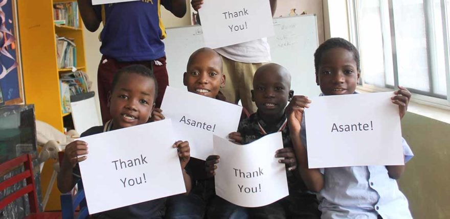 "Tanzanian children hold signs that say, ""Thank you!"" and ""Asante!"""