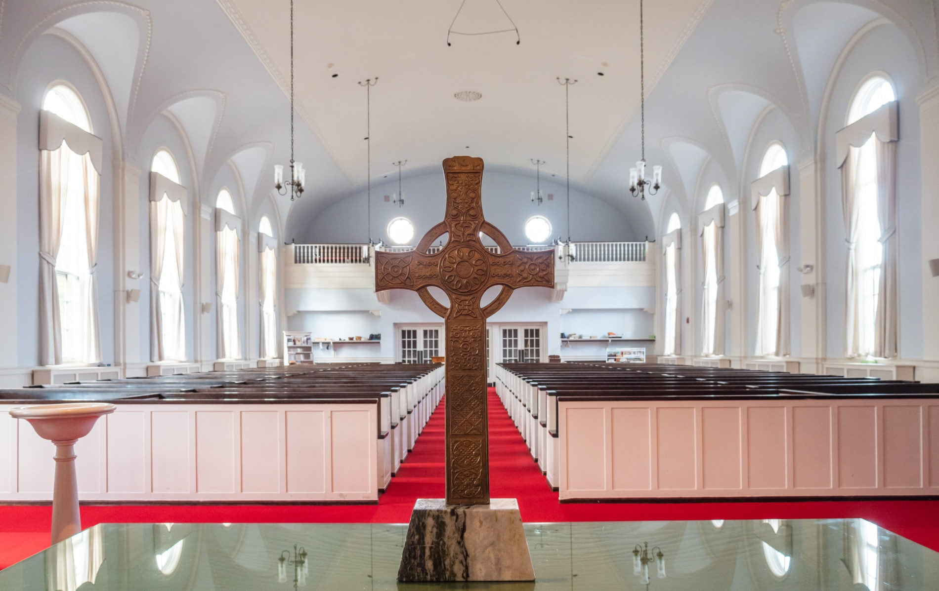 the cross on the communion table with the sanctuary behind