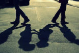 two pairs of legs are walking away from each other, but their shadows are about to embrace