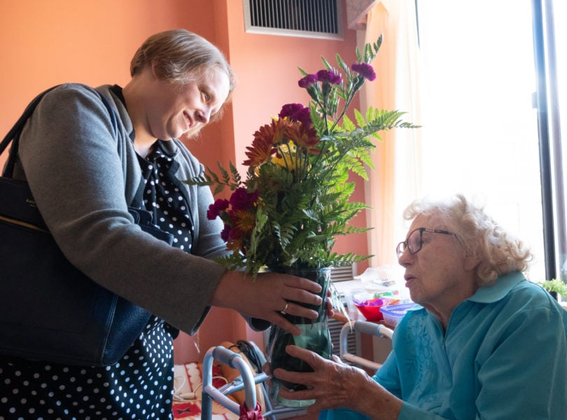 A woman delivers flowers to an elderly woman