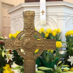A celtic cross stands in front of lilies and daffodils with the pulpit behind