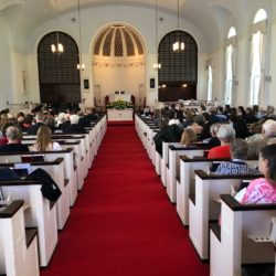 A view of people in worship from the back of the sanctuary