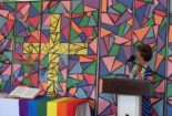 Dorothy Boulton preaches with a rainbow flag draped across the alter.