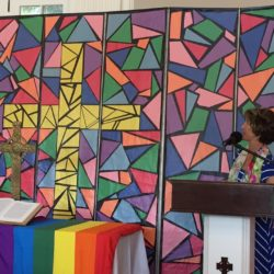 Dorothy Boulton preaches with a rainbow flag draped across the alter.