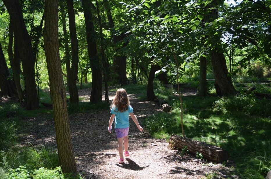 A girl walks down a sun-dappled path in the church woodlands.