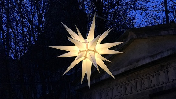 A Moravian star hangs against a dark sky