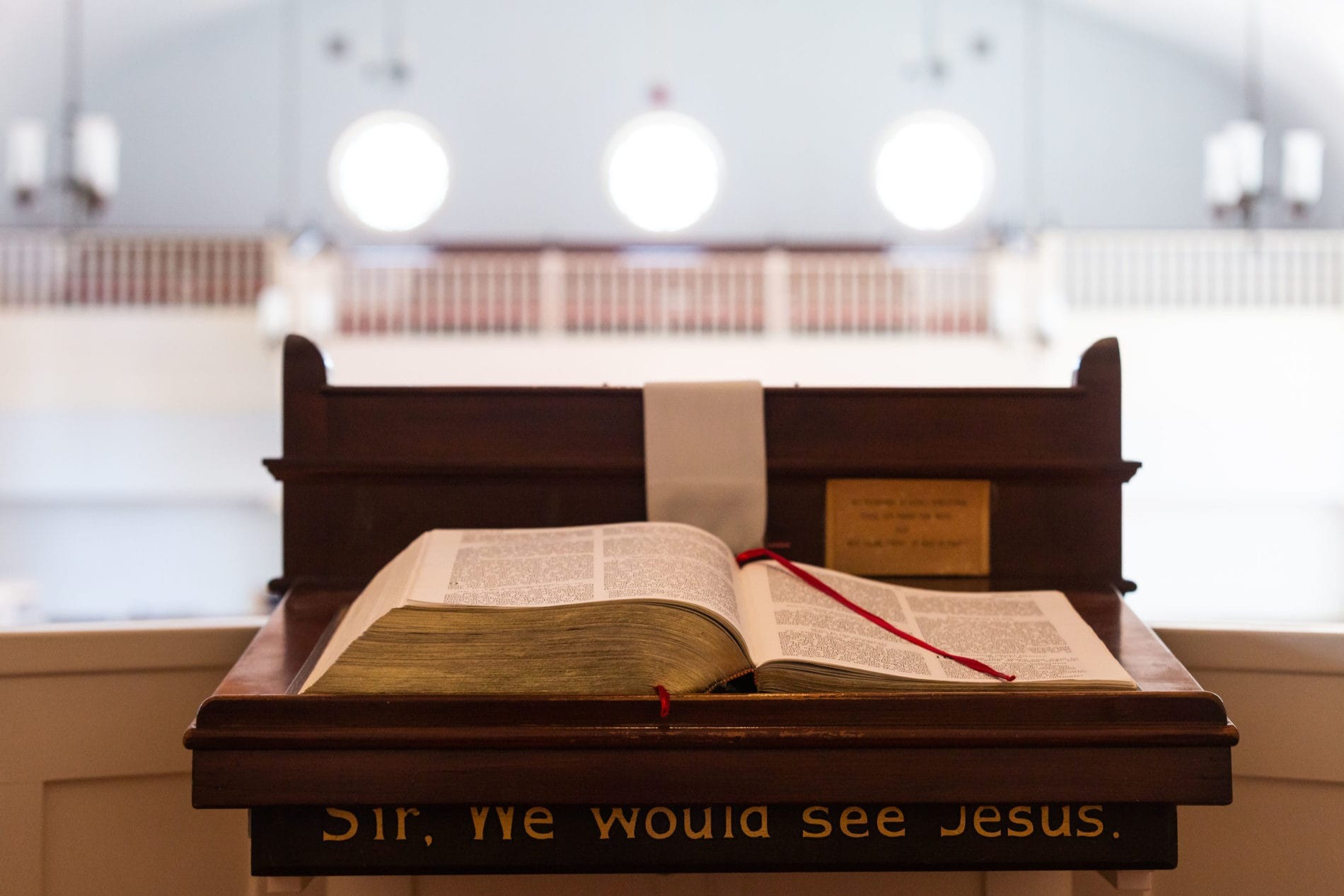 An open Bible sits on the pulpit. The words,