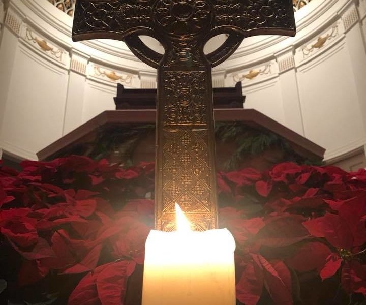 A candle sits in front of the cross and poinsettias