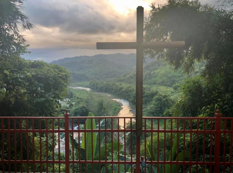 A cross overlooks a valley and river in Puerto Rico