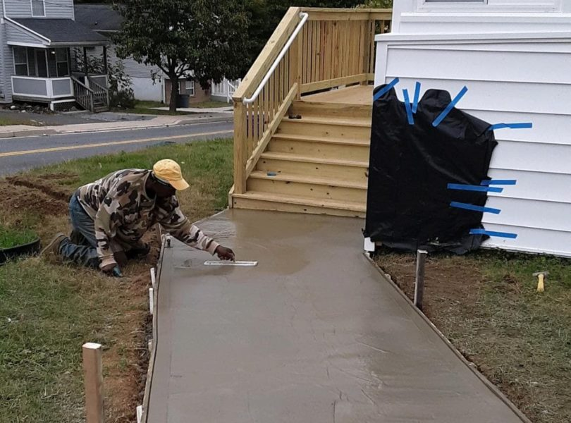 A worker smooths wet concrete on a new sidewalk.