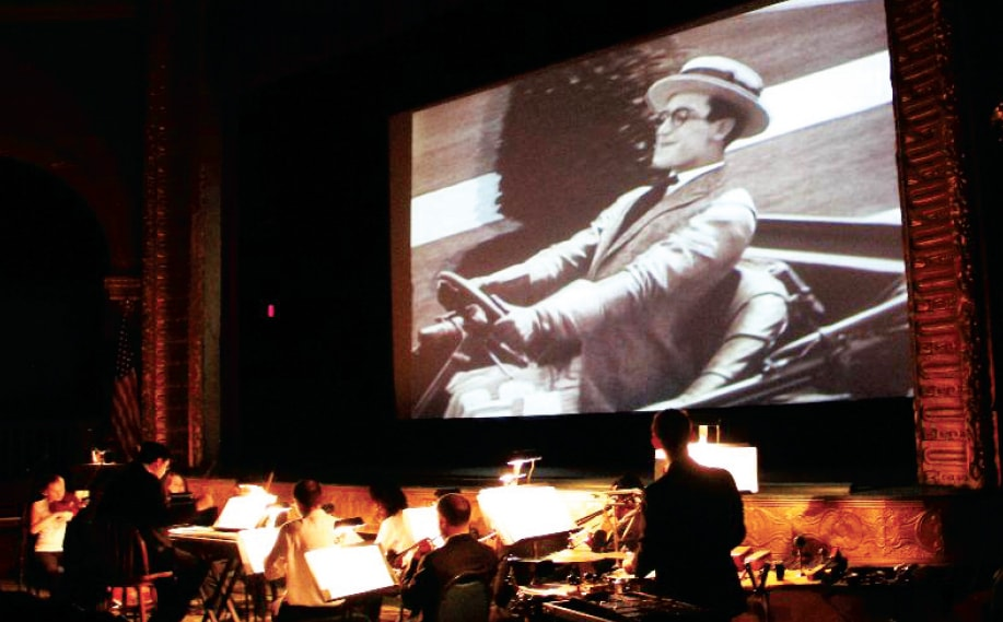 Peacherine Ragtime Society Orchestra plays in front of a silent movie