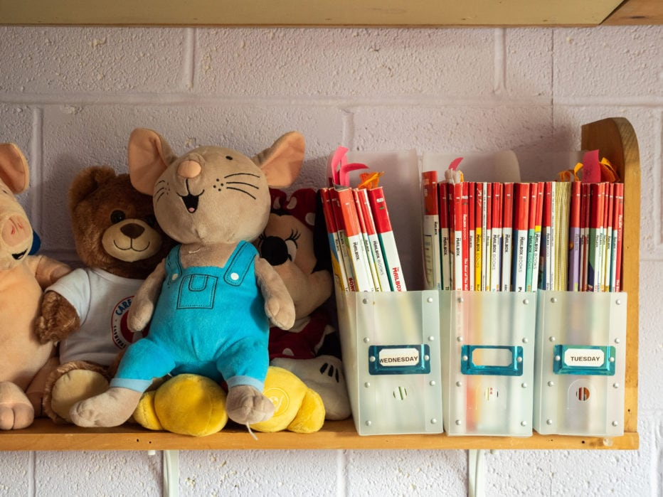 Toys and books sit on a shelf