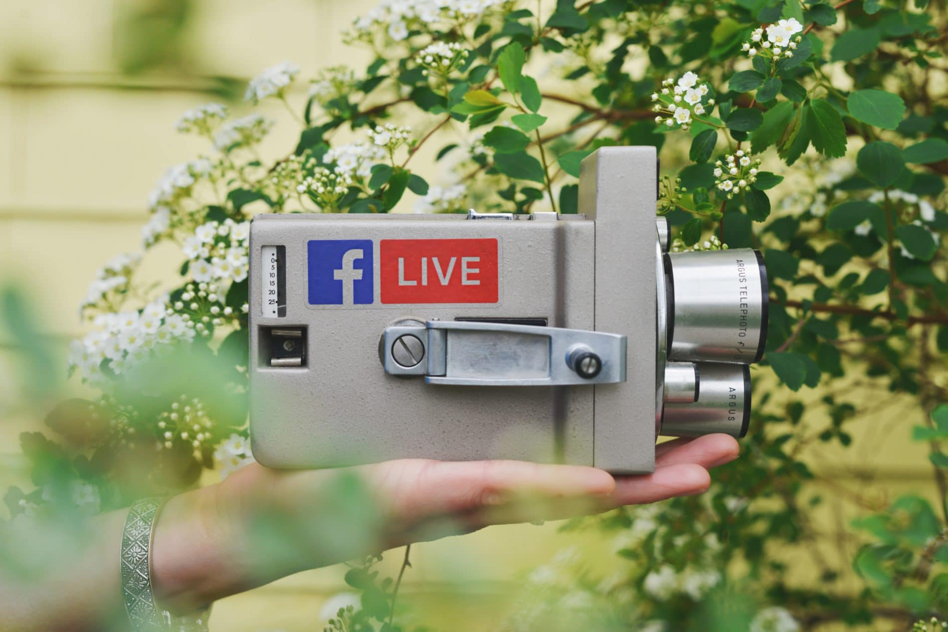 A hand holds a video camera with the logos for Facebook Live