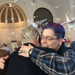 A woman with purple hair hugs a man with white hair