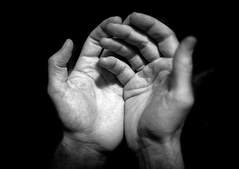 a black and white photo of open hands
