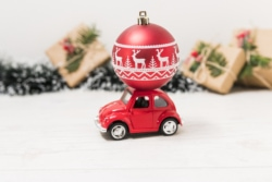 a red toy car has a red Christmas ornament on top