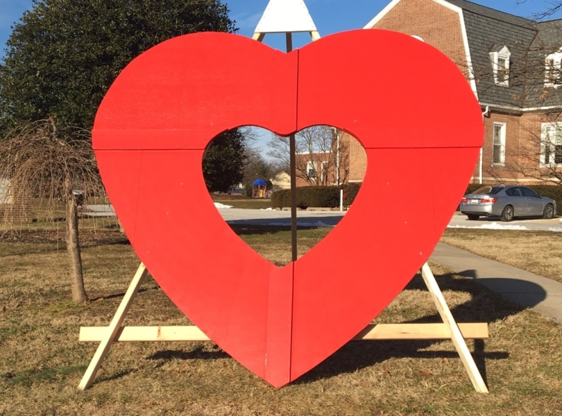 A large, wooden, red heart is displayed on the church lawn