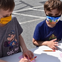 Two children do crafts outside
