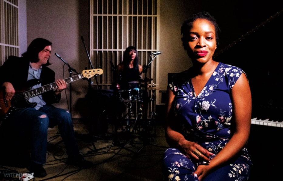 Joy Ike sits with a guitarist and drummer behind her