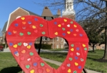 A large, red, wooden heart stands on the church lawn with small, multi-colored paper hearts scattered over it.