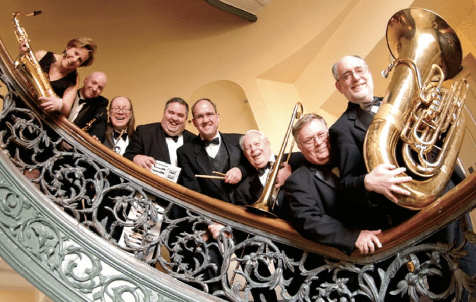 Peabody Ragtime Ensemble: 8 musicians hold their instruments and smile as they lean over a stair railing