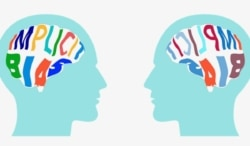 """Silhouettes of 2 heads with the words """"implicit bias"""" written on the brains"""