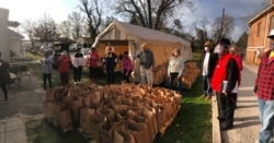 Volunteers stand around paper bags of food ready to distribute at Grace AME's Thanksgiving food drive.